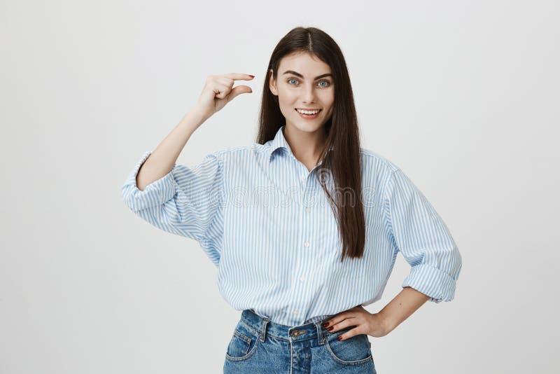 Studioporträt des netten europäischen weiblichen Unternehmers, der kleines oder kleines Zeichen mit den Händen ausdrücken Glück u lizenzfreies stockbild