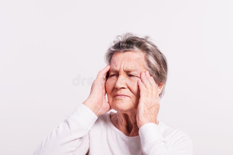 Studioporträt einer älteren Frau in den Schmerz lizenzfreie stockfotos