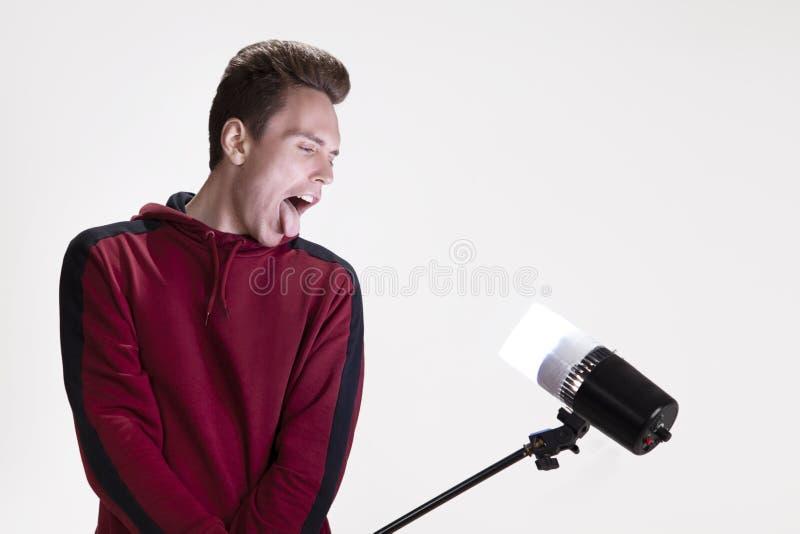Studioportr?t eines Kerls, der im Studio Gesicht verzieht, das einen Scheinwerfer in seinen H?nden h?lt lizenzfreies stockfoto