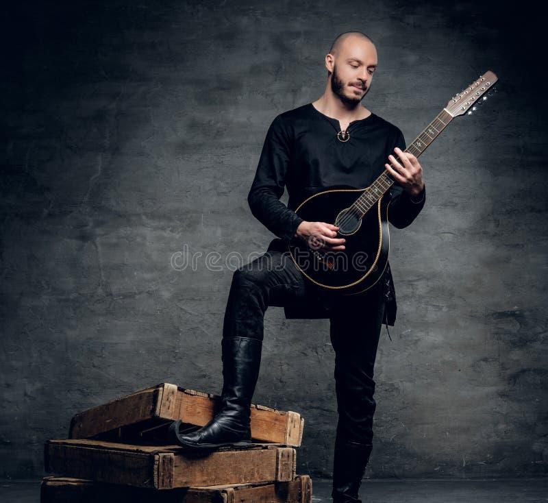 Studioporträt eines Mannes in der traditionellen keltischen Kleidung, die auf Mandoline spielt lizenzfreie stockfotografie
