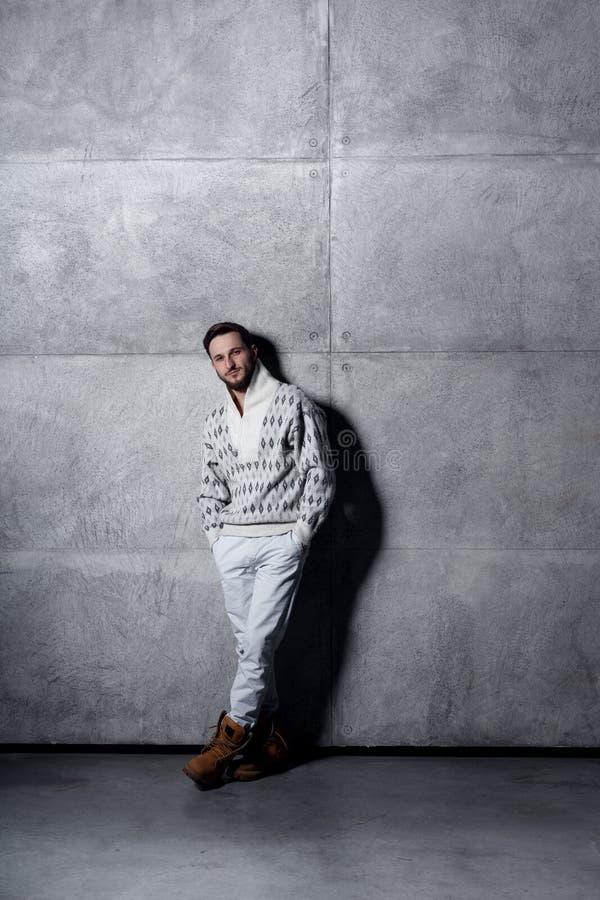 Studioporträt in voller Länge eines jungen Mannes in den weißen Jeans und in der Wolljacke, werfend über konkretem Hintergrund au lizenzfreie stockfotos