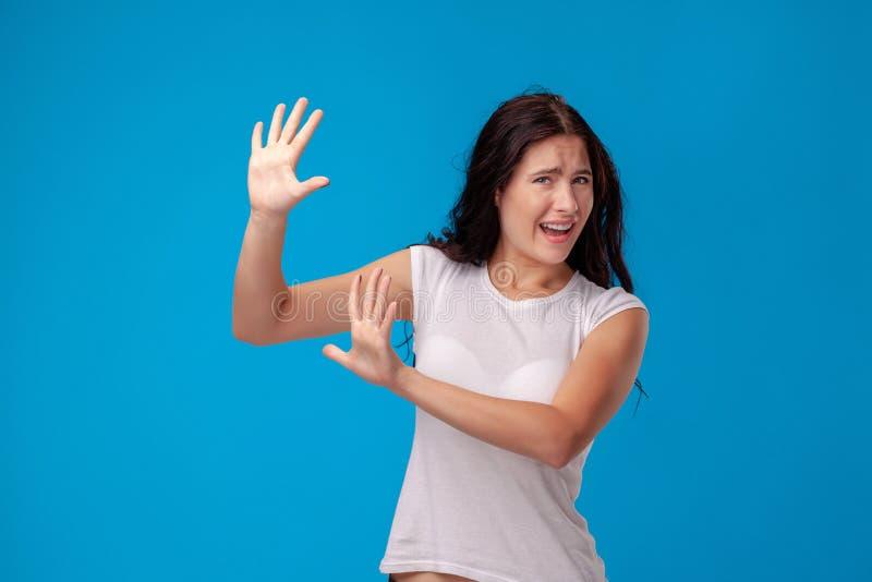 Studioportr?t einer jungen Sch?nheit in einem wei?en T-Shirt gegen einen blauen Wandhintergrund Aufrichtige Gef?hle der Leute lizenzfreie stockfotos