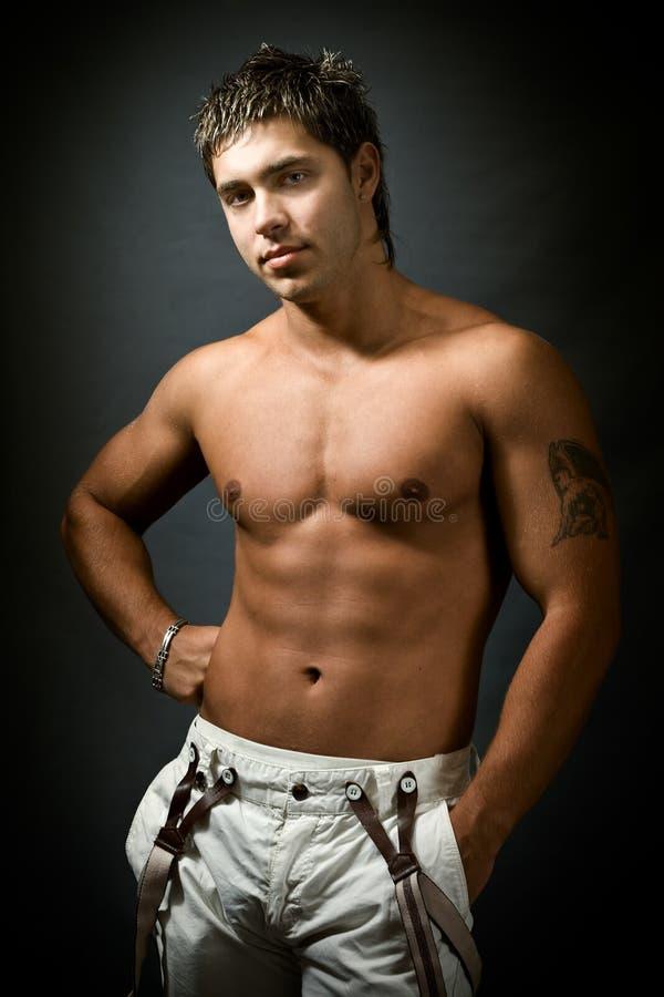 Studioportrait des mit nacktem Oberkörper reizvollen muskulösen Mannes stockbild