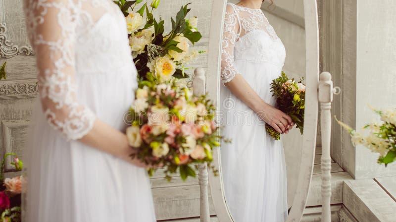 Studioportret die van een bruid die zich dichtbij een spiegel met een bezinning bevinden, in haar handen mooie bloemen houden royalty-vrije stock afbeeldingen