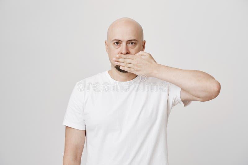 Studioportret die van ernstige kalme kale gebaarde mannelijke behandelende mond met hand en het bekijken camera, zich tegen grijs royalty-vrije stock foto's