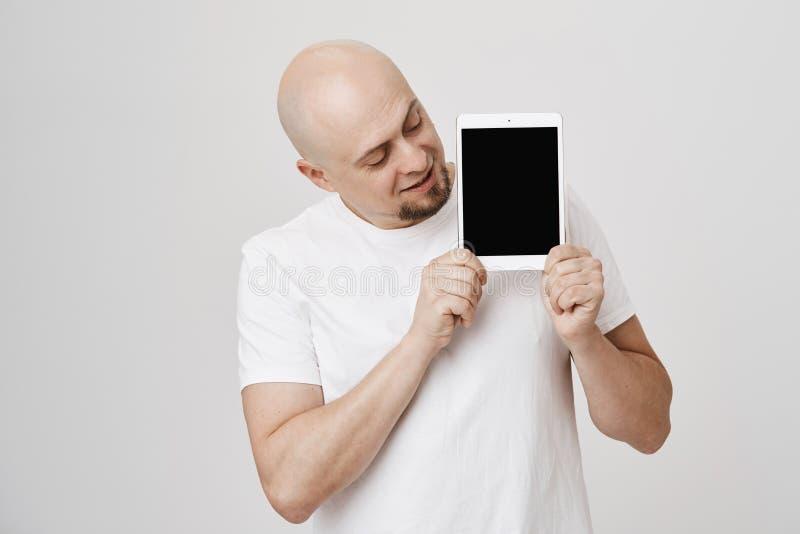 Studioportret die van gelukkig kaal volwassen mannetje met de tablet van de baardholding met beide handen, het tonen bij camera t royalty-vrije stock afbeeldingen