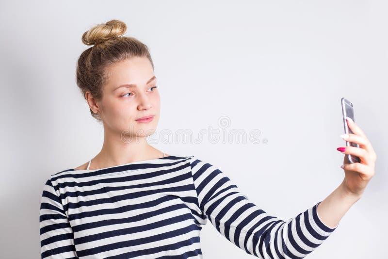 Studioportret die van het mooie blondevrouw glimlachen met witte tanden en het maken selfie, fotograferen over wit royalty-vrije stock foto's