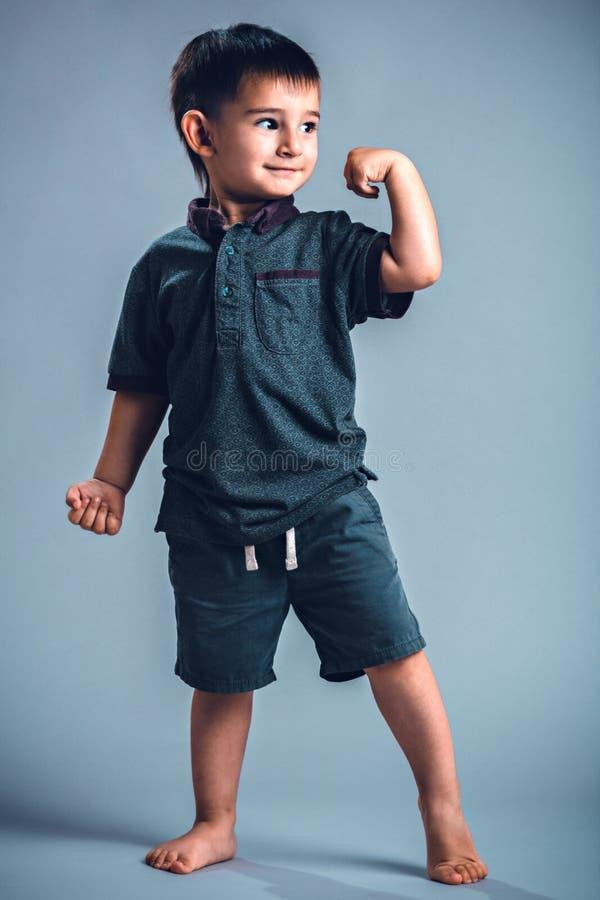 Studioportret die van wat jongen het stellen, spieren tonen royalty-vrije stock foto