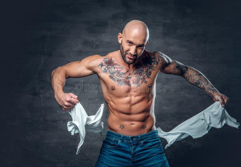 Studioportret van atletisch mannetje met een tatoegering op zijn borst ripp stock fotografie