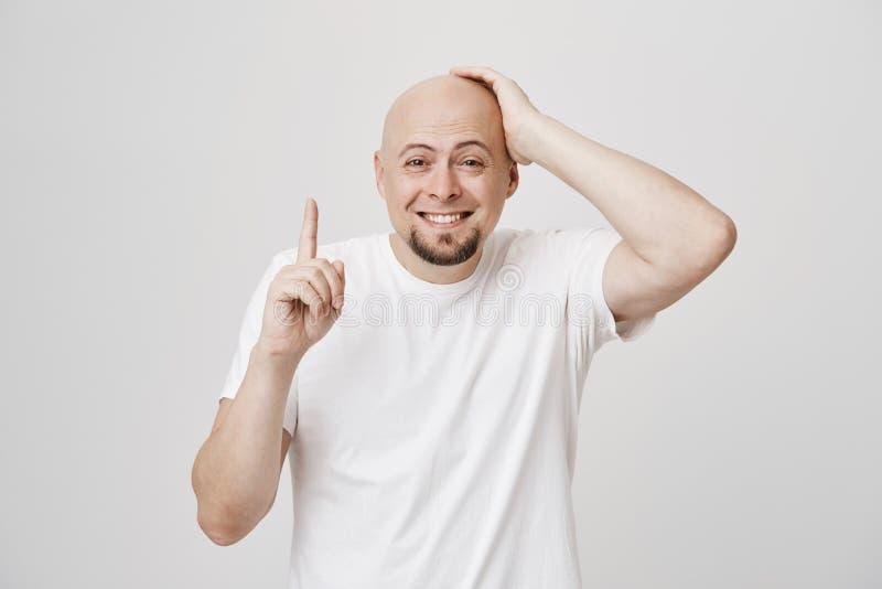 Studioportret van de aantrekkelijke enige kale mens met baard wat betreft hoofd terwijl het benadrukken en het glimlachen terwijl stock afbeelding
