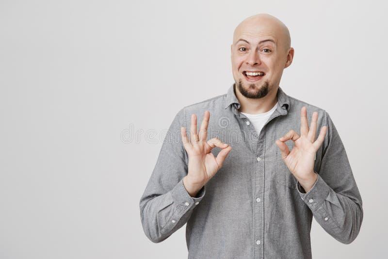 Studioportret van de blije kale knappe Europese mens met baard die o.k. of groot gebaar tonen terwijl ruim het glimlachen stock foto's