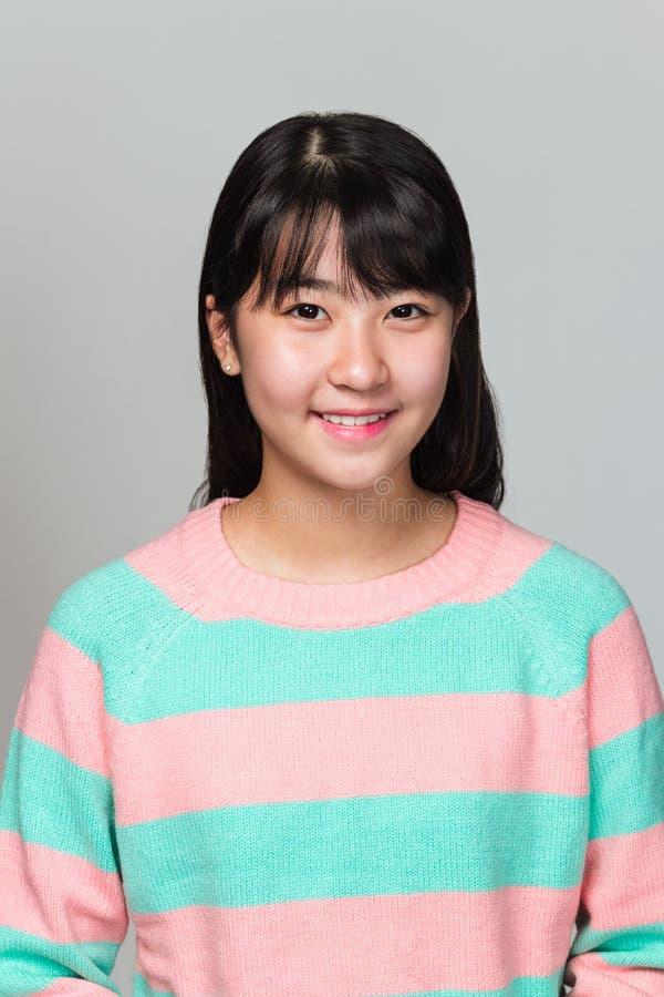 Studioportret van de gelukkige tiener Aziatische vrouw van het Oosten op grijze achtergrond royalty-vrije stock foto