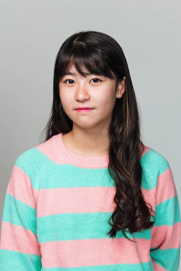 Studioportret van de gelukkige tiener Aziatische vrouw van het Oosten op grijze achtergrond royalty-vrije stock afbeeldingen