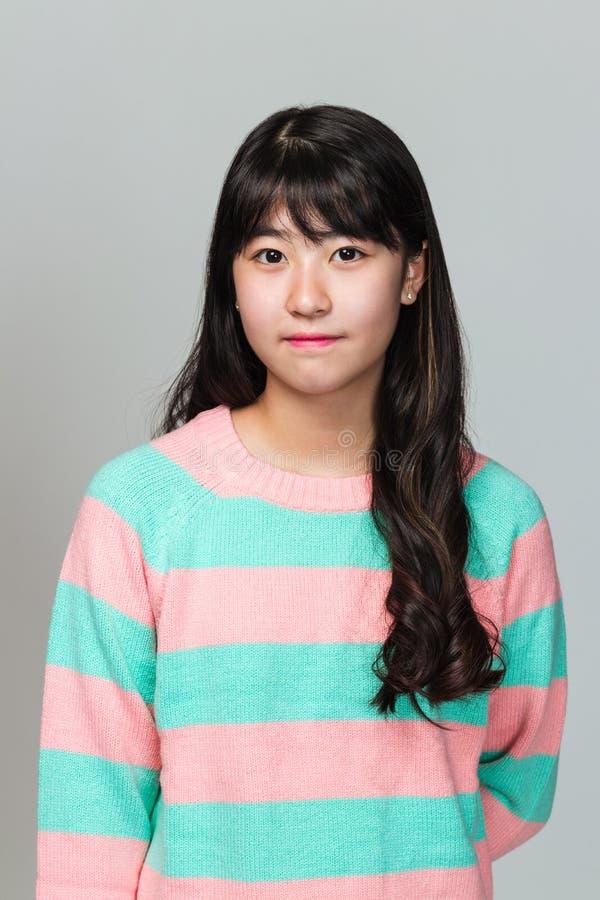 Studioportret van de gelukkige tiener Aziatische vrouw van het Oosten op grijze achtergrond stock foto's