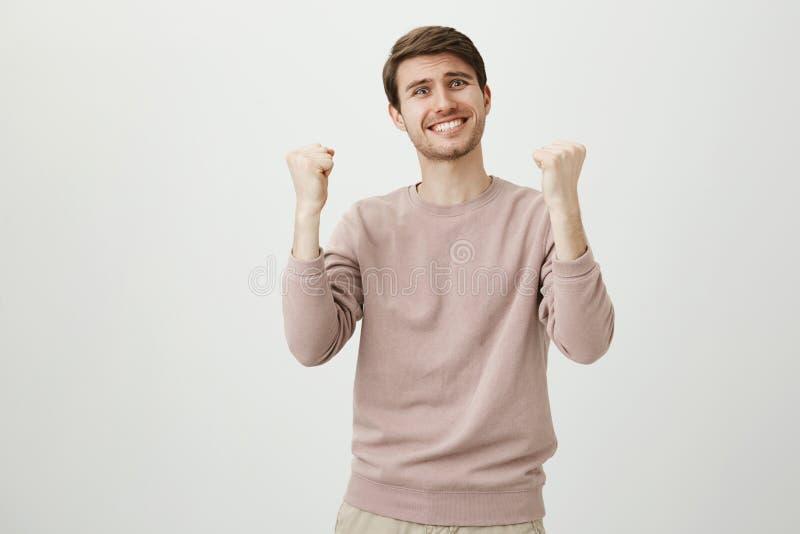 Studioportret van de grappige gevoels knappe mens die opgeheven vuisten clasping en wegens overwinning worden opgewekt of succesv stock afbeelding