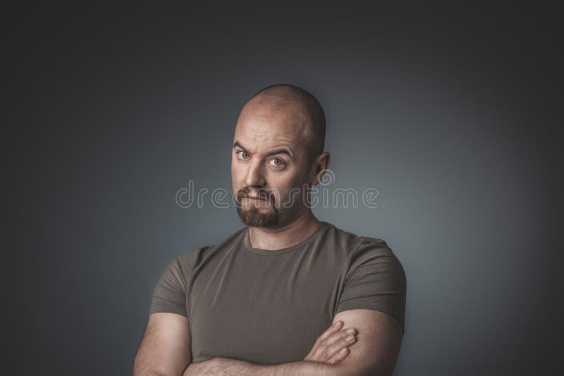 Studioportret van de mens met twijfelachtige uitdrukking en gekruiste wapens royalty-vrije stock foto's