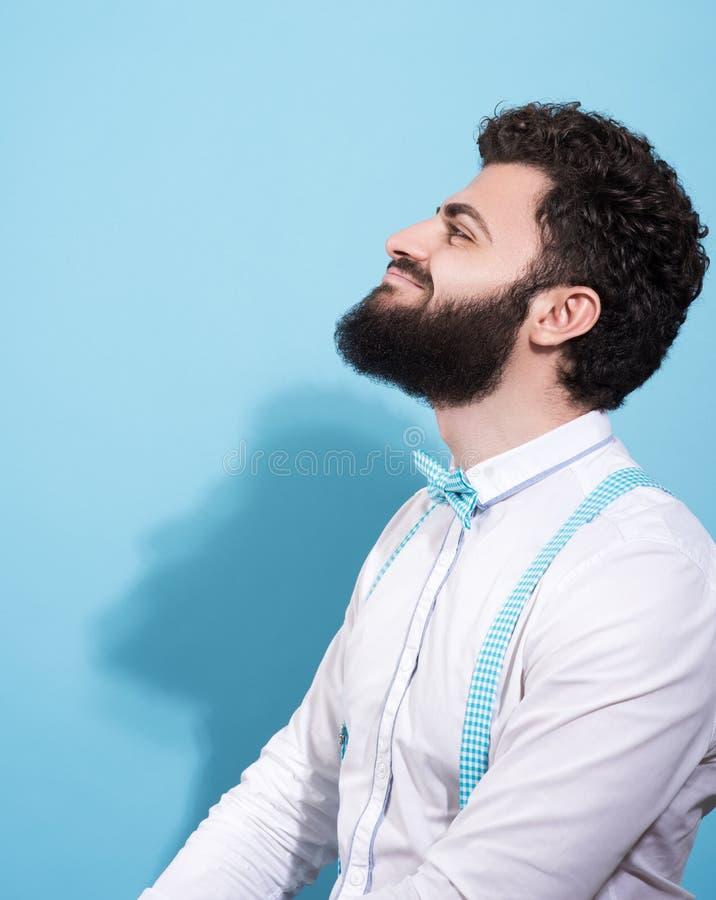 Studioportret van de vrolijke jonge mens in profiel Modieuze verschijning, een baard en een glimlach stock fotografie