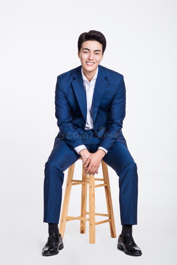 Studioportret van een jonge Aziatische bedrijfsmensenzitting als voorzitter stock fotografie