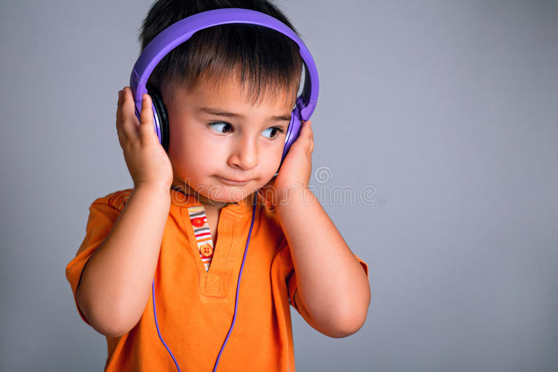 Studioportret van een kleine grappige jongen die met bruine ogen in hoofdtelefoons aan muziek op een grijze achtergrond luisteren royalty-vrije stock fotografie