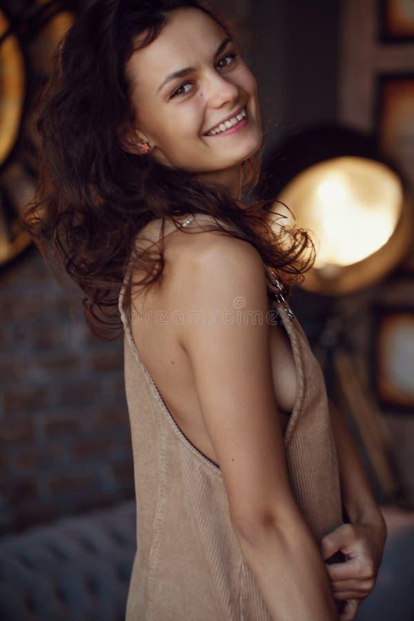 Studioportret van een mooi jong glimlachend meisje met bruin krullend haar Vrij modelmeisje met perfecte verse schone huid - Beel stock fotografie