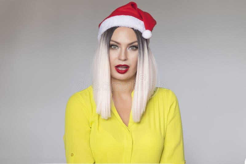 Studioportret van een mooie blondevrouw die Kerstmis rode hoed dragen stock afbeeldingen