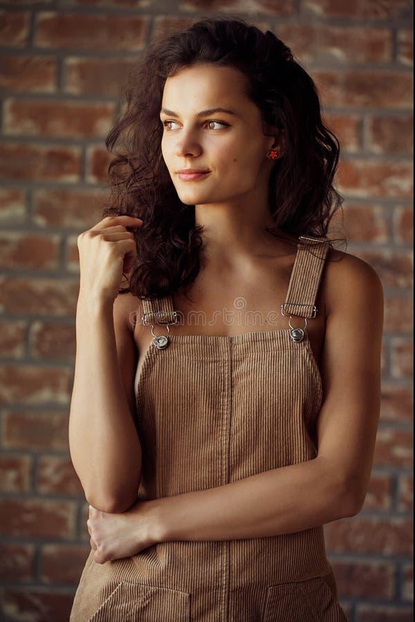 Studioportret van een mooie jonge vrouw met bruin krullend haar Vrij modelmeisje met perfecte verse schone huid - Beeld stock foto