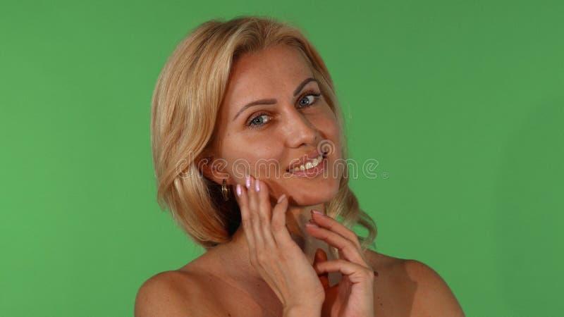Studioportret van een mooie rijpe vrouw wat betreft haar gezicht sensually stock foto's