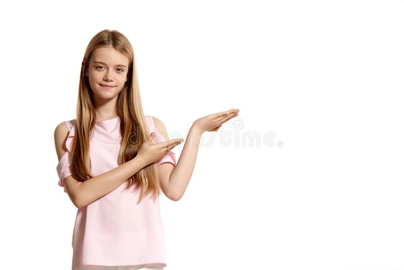 Studioportret van een mooie tiener van het meisjesblonde in het roze t-shirt stellen geïsoleerd op witte achtergrond stock fotografie