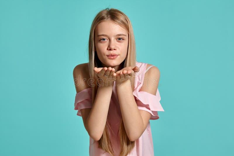 Studioportret van een mooie tiener van het meisjesblonde in het roze t-shirt stellen over een blauwe achtergrond stock afbeelding
