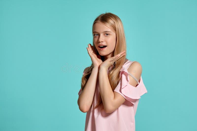 Studioportret van een mooie tiener van het meisjesblonde in het roze t-shirt stellen over een blauwe achtergrond royalty-vrije stock fotografie