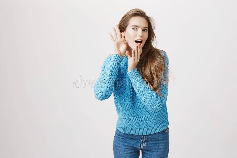 Studioportret van geïntrigeerde Europese vrouw die houdt van te roddelen, buigend naar camera met handen dichtbij oor en geopend stock afbeelding
