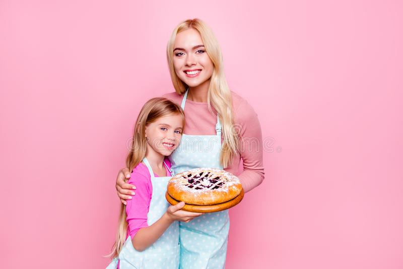 Studioportret van gelukkige moeder en dochter die gesteunde pastei met jam binnen voor vader samenhouden, die aan camera, bevinde stock afbeeldingen