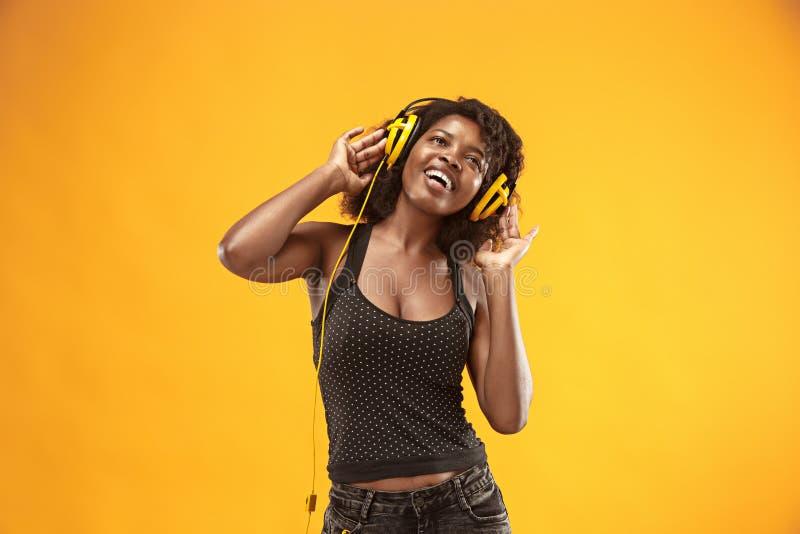 Studioportret van het aanbiddelijke krullende meisje gelukkige glimlachen tijdens photoshoot Het overweldigen van Afrikaanse vrou royalty-vrije stock afbeelding