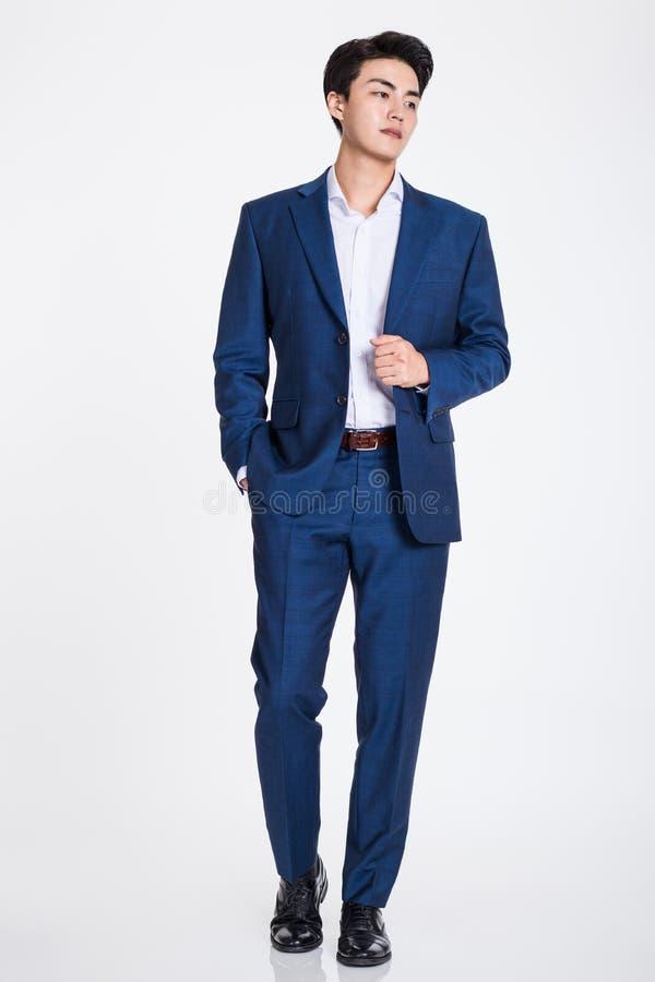 Studioportret van het zekere zakenman stellen tegen een grijze achtergrond royalty-vrije stock foto's