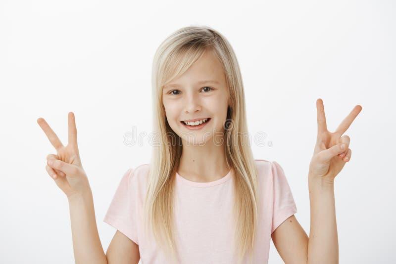 Studioportret van onbezorgd positief vrouwelijk kind met blond haar in toevallige uitrusting, die overwinning of vredesgebaren to stock afbeeldingen