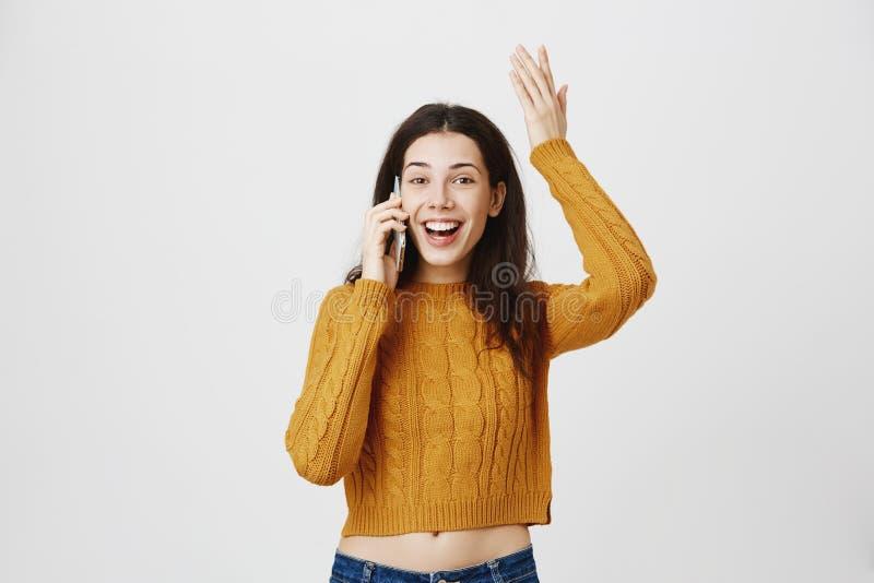 Studioportret van opgewekte en verbaasde vrouwen opheffende hand terwijl het spreken op smartphone, het uitdrukken van geluk en h royalty-vrije stock foto