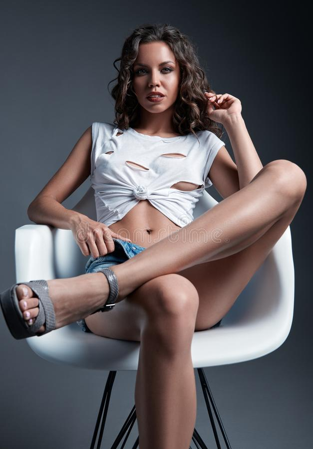 Studioportret van slank sexy mooi meisje De sensuele jonge vrouw kleedde zich in borrels en de zitting van de holeyt-shirt op sto stock foto's