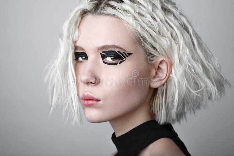 Studioschönheitsporträt der jungen Frau mit schwarzem grafischem Make-up stockbilder