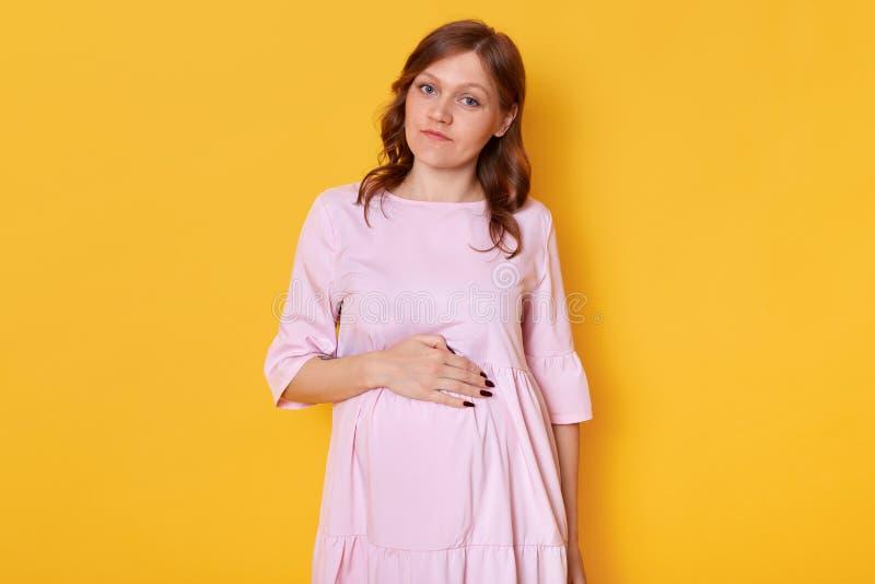 Studioschot die van jonge vrij zwangere vrouw die roze poederkleding dragen en hand op buik houden, direct camera bekijken met stock fotografie