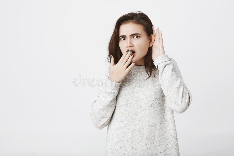 Studioschot die van Kaukasisch meisje met geschokte uitdrukking, haar mond behandelen en hand houden dichtbij oor om roddel te ho royalty-vrije stock foto's