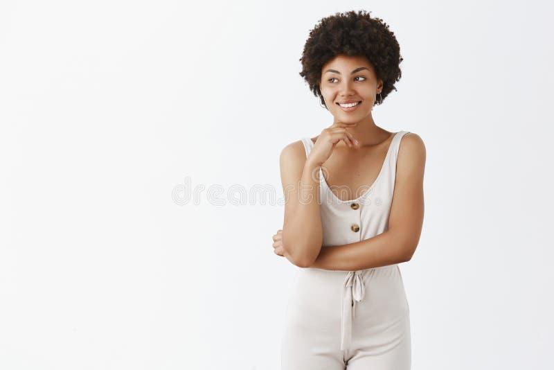 Studioschot van creatief aantrekkelijk donker-gevild meisje in modieuze overall met krullend kapsel wat betreft kin zacht en stock afbeelding