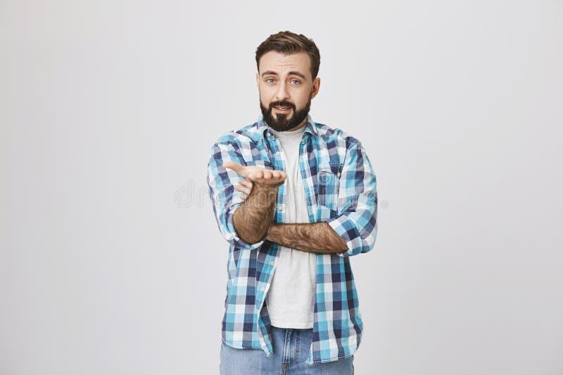 Studioschot van de aantrekkelijke Kaukasische gebaarde mens die rechtstreeks met palm richten en bereidheid uitdrukken om antwoor stock afbeelding