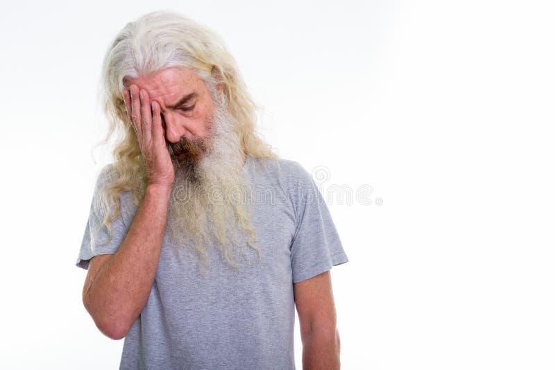 Studioschot van de beklemtoonde hogere gebaarde mens die hoofdpijn hebben stock afbeelding
