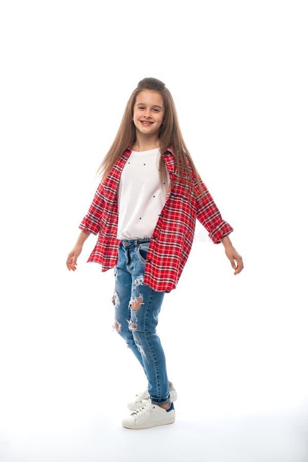 Studioschot van een glimlachend meisje die in jeans dragen en een rood gecontroleerd overhemd op een witte achtergrond Zij stelt  stock fotografie