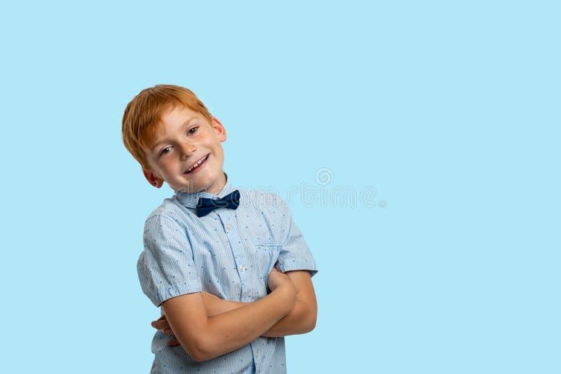 Studioschot van een glimlachende roodharigejongen die blauw overhemd met boog dragen tegen blauwe achtergrond met exemplaarruimte royalty-vrije stock afbeeldingen