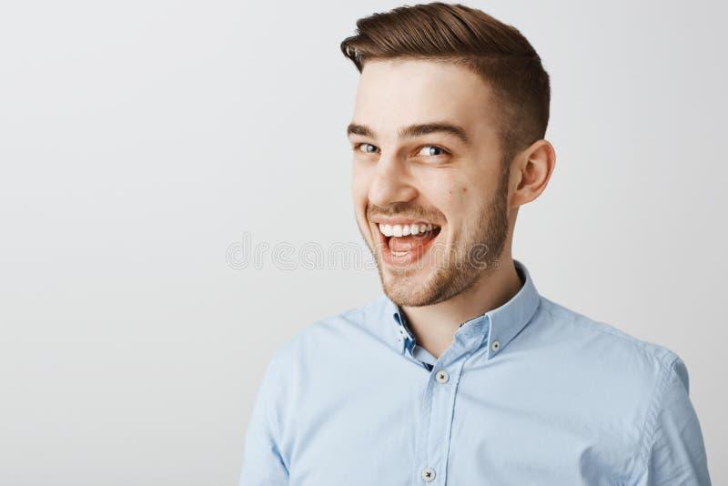 Studioschot van geamuseerde geheimzinnige knappe kerel met varkenshaar en modieus kapsel die bij iets het ontzagwekkende glimlach stock fotografie