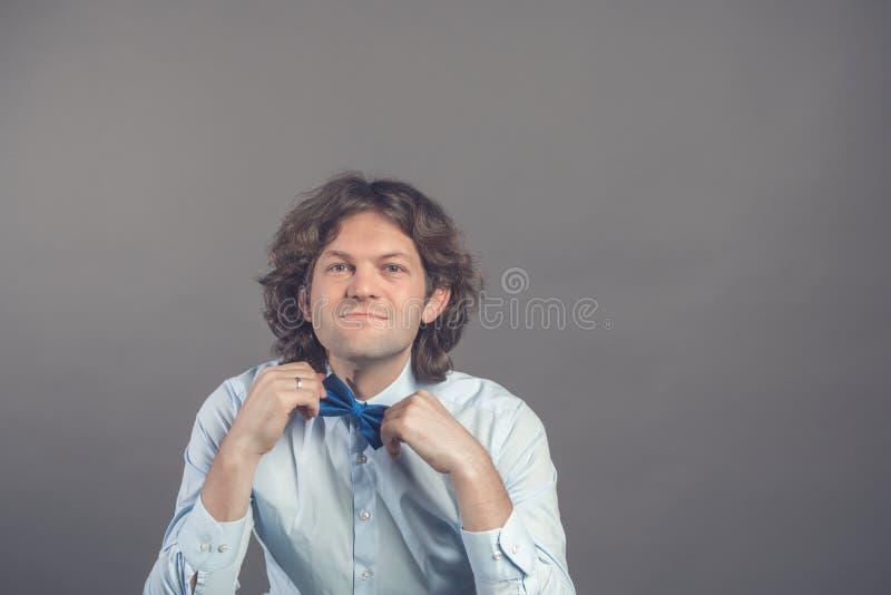 Studioschot van jong mannetje die hipster zijn die vlinderdas in spiegel aanpassen op grijze achtergrond wordt geïsoleerd Donkere royalty-vrije stock afbeeldingen