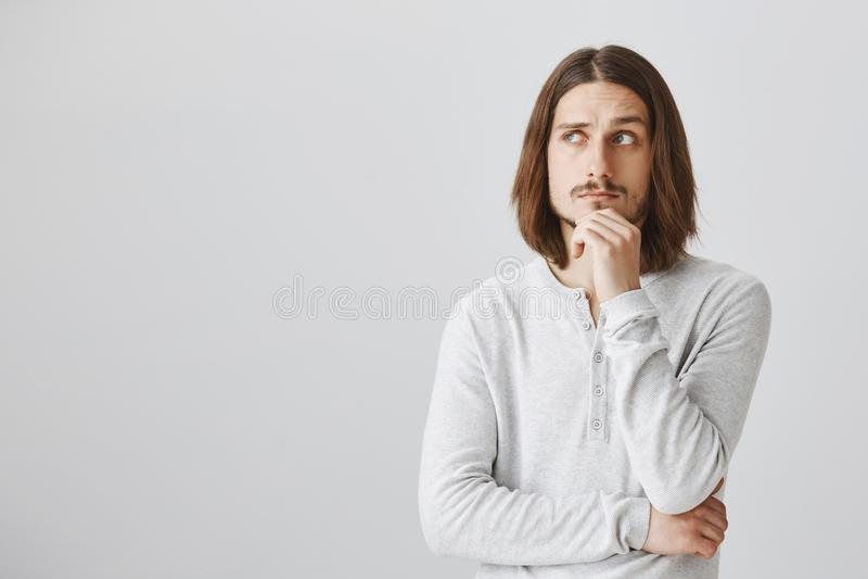Studioschot van knappe slimme kerel met de lange eerlijke hand van de haarholding op kin en omhoog het kijken, binnen het denken  royalty-vrije stock afbeeldingen