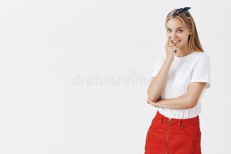 Studioschot van nieuwsgierig knap modieus Kaukasisch meisje met eerlijk haar in hoofdband en in rode rok, het bijten royalty-vrije stock fotografie