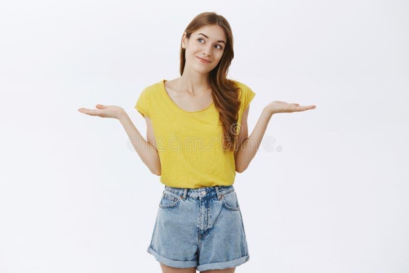 Studioschot van onbewust onbezorgd knap gembermeisje die in gele t-shirt met uitgespreide handen ophalen opzij het glimlachen en stock fotografie